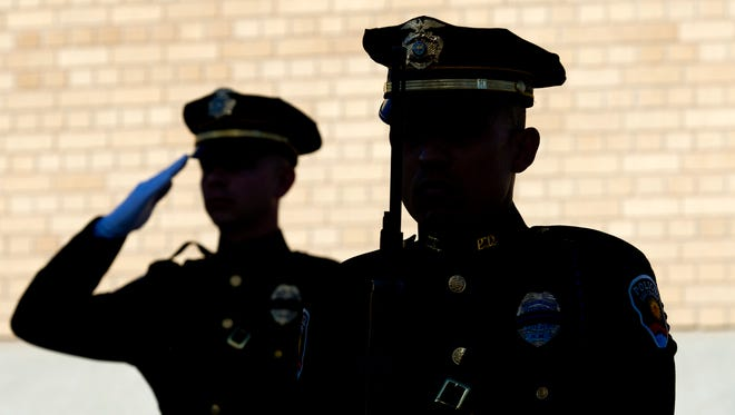 Las Cruces Police Department Honor guard members Aaron Glymph, left, and Eric Urends, salute after a 21-gun salute was fired at the Patriot Day celebration Sunday, Sept. 11, 2016, at the Plaza de Las Cruces.
