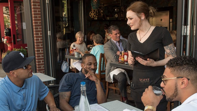 Courtney McManus takes orders from Anthony Warren, Brandon Jackson, ans A. Joseph, seated on the outdoor patio at Toast, in Birmingham.