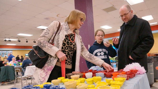 Garden City school board president Darlene Jablonowski, Chief Financial Officer Drew McMechan and his 9-year-old daughter, Avery look at the display of empty clay bowls.