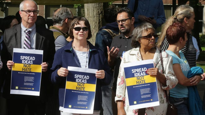Michael Imperiale, a professor of micro biology and immunology, left,  Michelle Pardee , a clinical assistant professor of nursing,  and Patricia Coleman-Burns, a  emerita professor of nursing, all of the University of Michigan, are gathering together with other faculty, staff and students to take a stand against hate and racism at The Diag on campus in Ann Arbor Tuesday, Oct. 4, 2016.