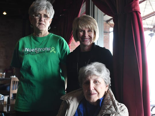 "Hattiesburg Councilmember Mary Dryden, top right, her sister Joan Goss, left, and her mother Carol Hickman, bottom, in The Thirsty Hippo, site of a dry cleaning shop belonging to Dryden's grandfather, beginning in the 1940s. The window behind them still bears the ""Sanitized"" label from the days of the shop."