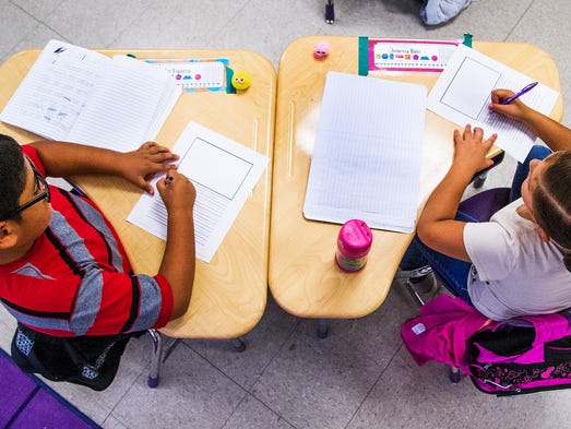 Kindergarten students do their work in class at the