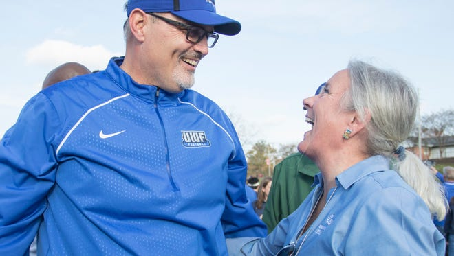 President Martha Saunders, right, congratulates head coach Pete Shinnick after the Argo victory over West Alabama in the playoff football game in Livingston, Alabama on Saturday, December 2, 2017.