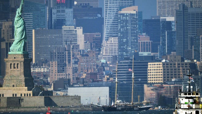 The 120-foot-tall schooner, Clipper City, center, rests stranded near the Statue of Liberty after running aground and getting stuck in shallow water in New York on Saturday. No injuries were reported and the 121 tourists onboard were ferried in small boats to a lower Manhattan marina.