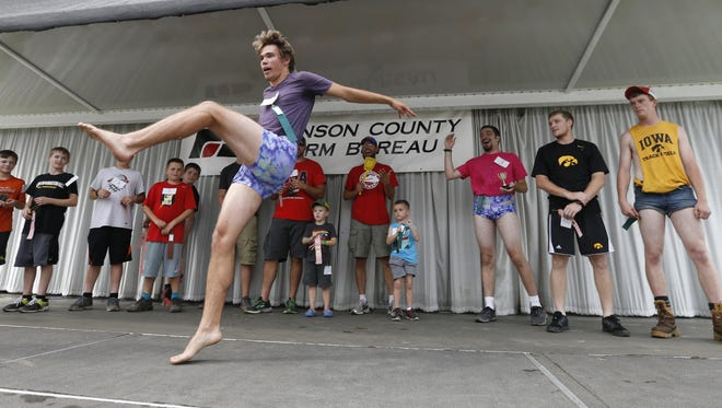 Riley Johanson of Oxford leaps to the center of the stage to receive his award for most muscular legs Tuesday, July 28, 2015, during the Mr. Legs competition at the Johnson County Fair in Iowa City.