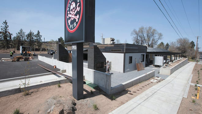 In this April 25, 2018 photo,  mason Joey Boisineau, center, checks the door on one of the outdoor fireplaces he built on the deck of the new Boneyard Pub, under construction in Bend, Ore. At a time when craft breweries compete more than ever for shelf space and tap handles in pubs, industry sales are leveling off, even in Bend, known as Beer Town USA.