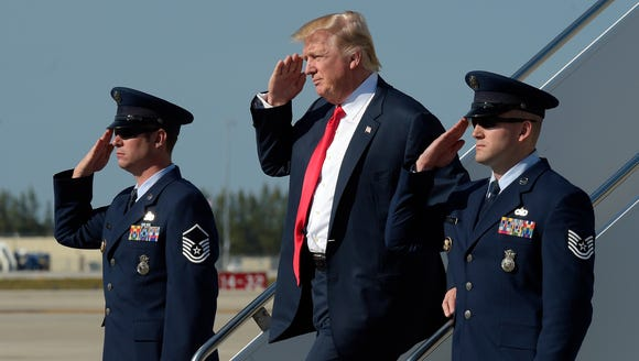 President Donald Trump salutes as he arrives a Palm