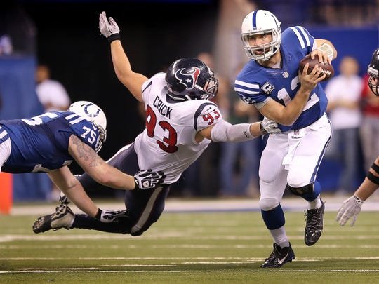 Colts quarterback Andrew Luck (12) runs away from the charging Texans defensive end Jared Crick (93) in the second half Sunday.