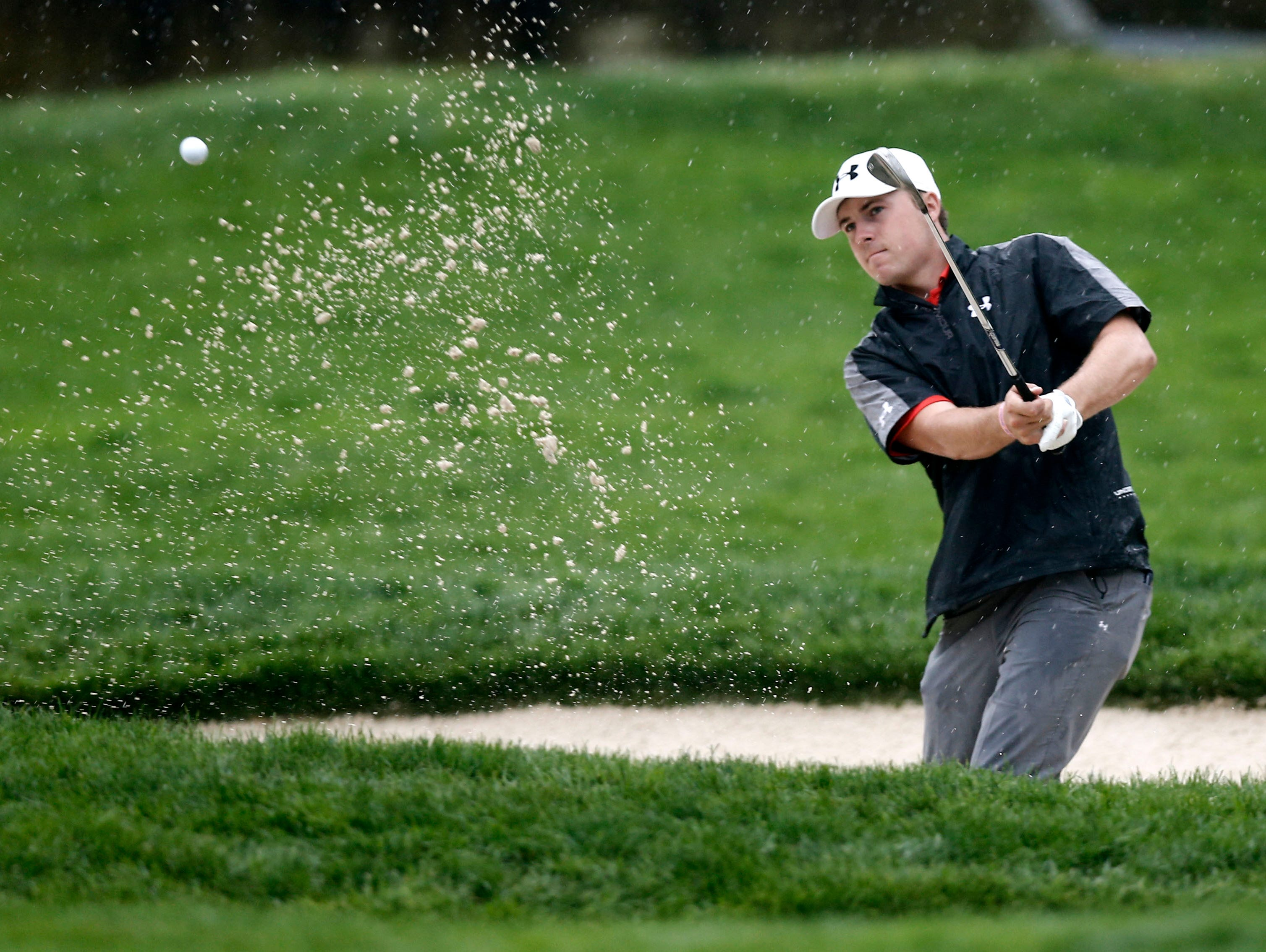 Jordan Spieth plays out of a greenside bunker on the 11th hole.