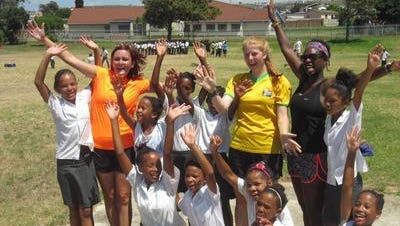 Cape Henlopen grad Domineque Scott (standing, second from right) poses with a class of students from South Africa.