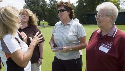 Kathy Wisne and Shannon Wisne-Helton talk with Meg Mallon and Sister Regina Doelker, the former principal at Mercy High School.