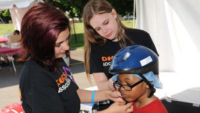 Kohl's volunteers Izabella Bowles and Hannah Kero fit Devin Robinson with a new bike helmet at last year's Passport to Safety event.