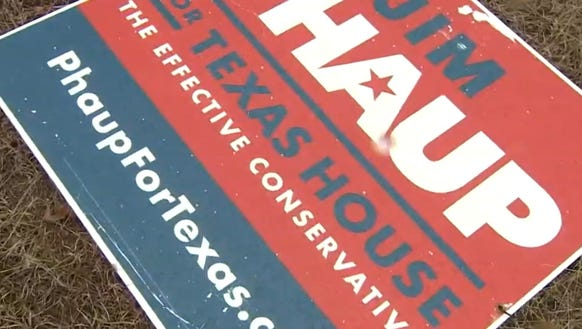 A campaign sign for Jim Phaup lies on the ground Feb.