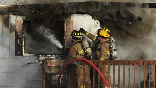 Unadilla Twp. firefighters battle flames and smoke at the front of a home on M-36, east of Gregory.