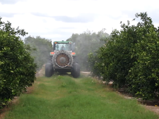 File photo of sprayer applying nutritional product onto foliage in a Southwest Florida citrus grove.