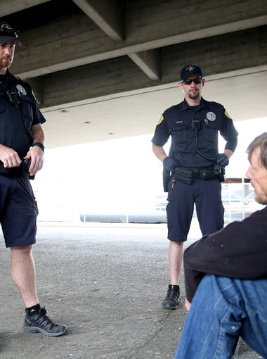 Salem Police Officers Andrew McFerron, left, and Zackary Merritt talk with Jonathan Jones, 49, who has been homeless in Salem for more than a year under the Center Street bridge in downtown Salem on Friday, May 25, 2018. Officer McFerron gave Jones a warning for trespassing after checking in with his patrol officer.