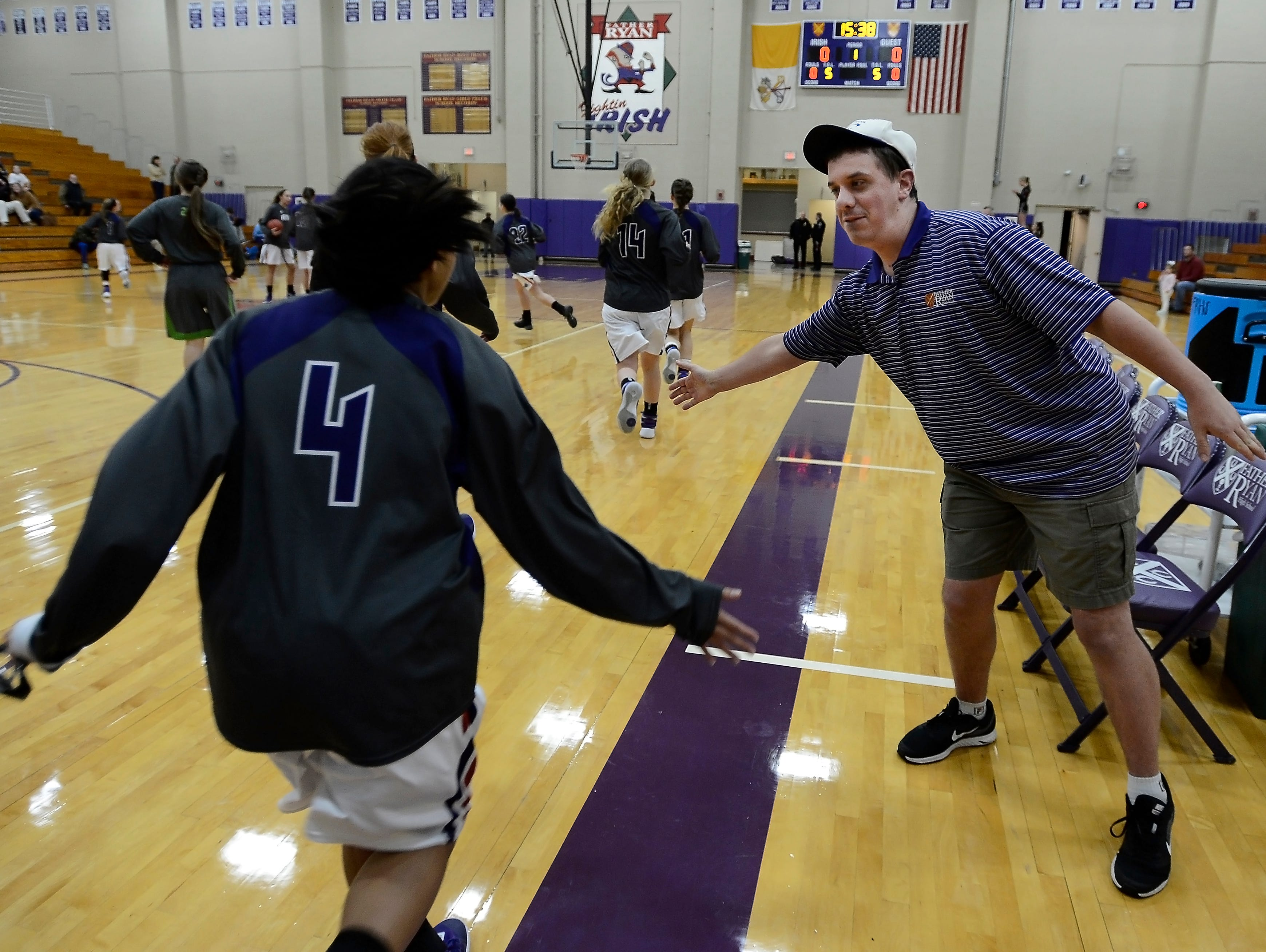 Sean Druffel slaps hands with Father Ryan High School girls varsity basketball player Adee Embry as the team runs onto the court for warm ups before a basketball game on Jan 5 in Nashville.