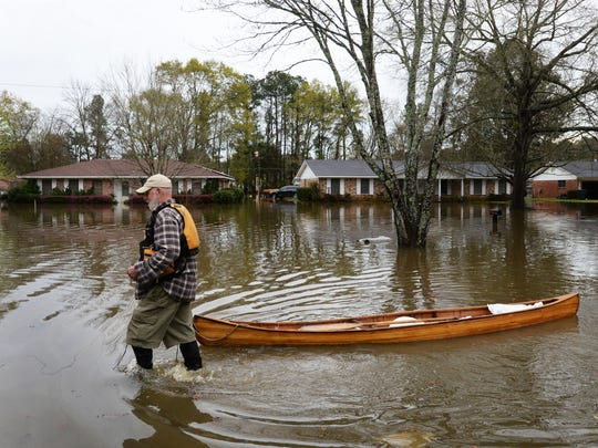 Richard Maxwell helps neighbors by carrying sandbags by canoe to their house to help prevent flooding inside the home on Dianne Street just south of Caddo Lake in Shreveport, Louisiana.