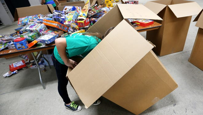 Volunteer Olivia Vaught, 12 of Brownsburg, has to go deep into a tall box to find more toys during the 2013 Toys For Tots drive sponsored by the Avondale Meadows YMCA and the Marine Corps at the Indiana State Fairgrounds on Saturday, December 21, 2013. Around 100 volunteers will be helping with the toy distribution for more than 4,500 kids.