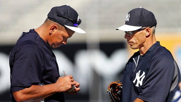 Alex Rodriguez of the New York Yankees autographs a ball as manager Joe Girardi looks on before the start of a MLB baseball game against the Los Angeles Angels of Anaheim at Yankee Stadium on August 14, 2013 in the Bronx borough of New York City.
