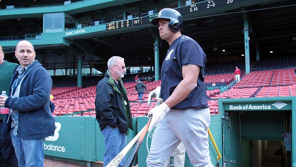 Brian Cashman of the New York Yankees watches as Alex Rodriguez prepares for batting practice before a game with Boston Red Sox at Fenway Park May 1, 2015 in Boston, Massachusetts.