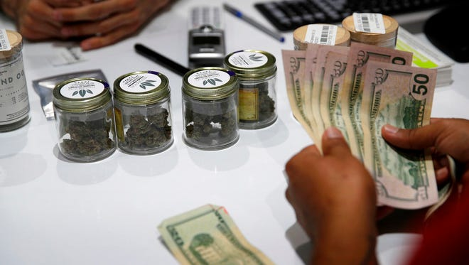 In this July 1, 2017 file photo, a person buys marijuana at the Essence cannabis dispensary in Las Vegas. Many employers across the country are quietly taking what once would have been a radical step: They're dropping marijuana from the drug tests they require of prospective employees.
