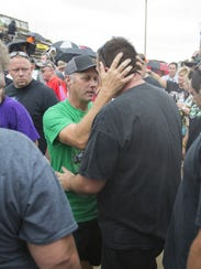 Tim Clauson (middle), embraces well-wishers at a tribute