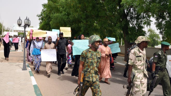 Soldiers lead the way as Chibok residents carry placards to protest the abduction of the missing schoolgirls, on Saturday in Maiduguri.