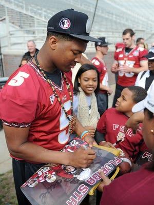 Florida State Seminoles quarterback Jameis Winston (5) signs autographs during the BCS National Championship Celebration at Doak Campbell Stadium.