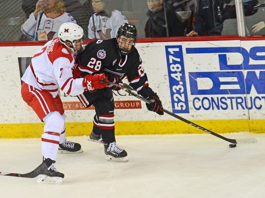 St. Cloud State's Kevin Fitzgerald (28) protects the puck against Miami's Grant Frederic on Saturday in Oxford, Ohio. The Huskies swept the RedHawks for the first time on the road with a 4-0 victory.