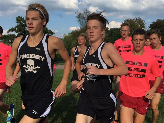 Pinckney's Aaron Jarema (left) and Ryan Talbott lead a pack of Milford runners. Talbott took first and Jarema second, but Milford won the meet.