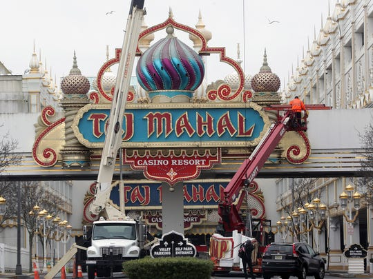 Serge Bycov, of Philadelphia, removes the Trump name from a sign at the entrance of the former Trump Taj Mahal casino in Atlantic City on Feb. 15