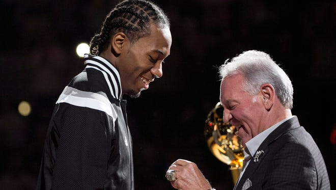 San Antonio Spurs small forward Kawhi Leonard (2) gets his NBA championship ring from San Antonio Spurs owner Peter Holt before the first game of the season.