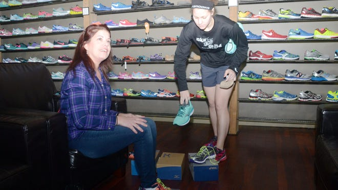 ANI Shopping Friday Amber Thomas (right), sales associate at Run Wild located on Jackson Street Extension, helps Theresa Hood as she tries on running shoes. Run Wild is one of the local businesses participating in Small Business Saturday. Friday, Nov. 28, 2014. -Melinda Martinez/mmartinez@thetowntalk.com, The Town Talk, Gannett
