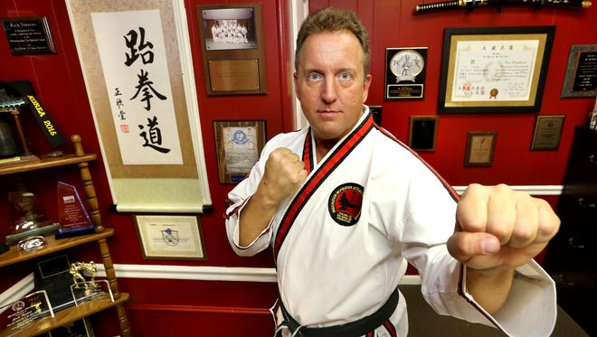 Jacks Stevens, Jr. the owner and master instructor of Stevens Family Tae Kwon Do, poses in his office with many of his trophies, awards and memorabilia, on Thursday, Sept. 3, 2015.