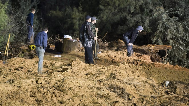 Workers dig out mud and debris after a flash flood in Hildale, Utah, on Tuesday,  Sept. 15, 2015. Rushing water washed away two vehicles, killing eight people Monday, Sept. 14, 2015.