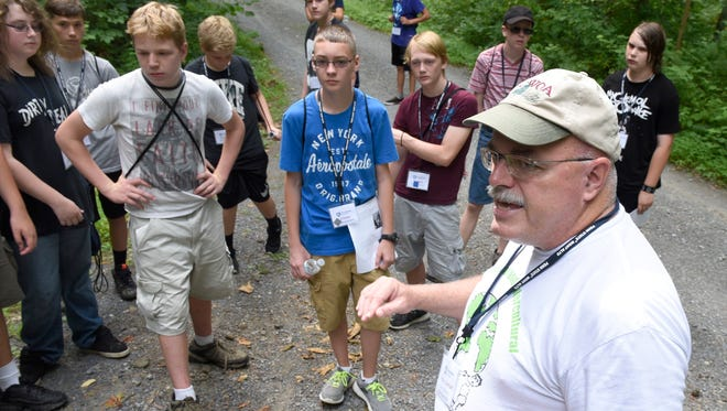 Peter Linehan, right, teaches students about geocaching as they walk through the woods behind campus on Friday, July 15, 2016. Students spent a week learning about building web pages and geocaching during the Penn State Mont Alto STEM Camp.