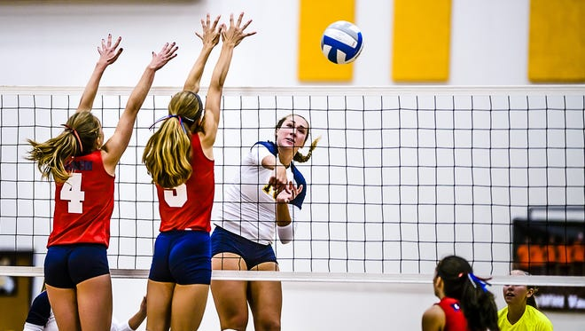 Lexi Nordman, center, of DeWitt hits around a Mason block during their match Wednesday September 7, 2016 in DeWitt.  Nordmann, a Southern Methodist University commit, is one of 10 finalists for Michigan Miss Volleyball.