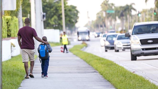 A man walks a child to Crosspointe Elementary School in Boynton Beach in August 2019.