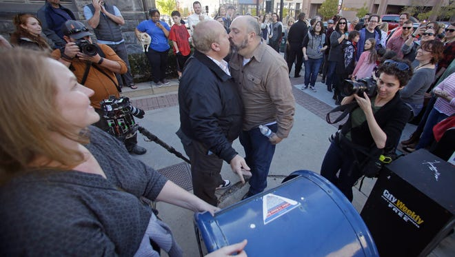 Mark Lindsay, left, and Tom Kerns kiss after mailing a resignation letter as Mormons gather for a mass resignation from the Church of Jesus Christ of Latter-day Saints Saturday in Salt Lake City.