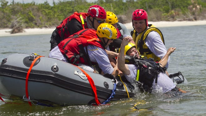 Jason Martin, left, John Nichols, front, Terry Brunson and Brian Dubrasky pull Phil Brown into the boat during a flood/swiftwater training exercise for the Southwest Florida Urban Search and Rescue Florida Task Force 6 at New Pass off Fort Myers Beach.