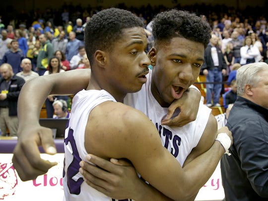 Ben Davis's Joshua Brewer (22), left, is hugged by Aaron Henry (50) following their win their IHSAA boys semistate basketball game Saturday, March 18, 2017, afternoon in Seymour, Indiana. The Giants defeated Castle, 74-71.