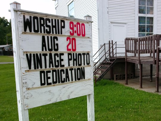 A sign promotes the photo exhibit at Center Lisle Congregational