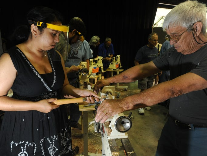 Erica Hazra of Atlanta, GA. is helped by Bill Engels  in making a honey dipper as crafters shared their art and  skills  with live demonstrations and offered hands on action for visitors during Wood Day at the Folk Art Center Saturday.  8-9-14