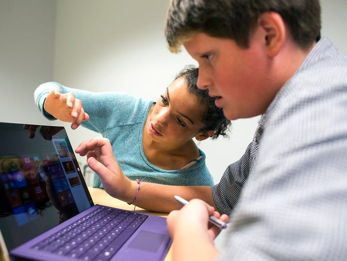 Keaisha Barnard, 13, left, shows Jackson Taylor, 14, different settings he can choose for his Windows Surface Pro tablet during the first day of school at Nesbitt Discovery Academy in Asheville, Wednesday, Aug. 20, 2014. The academy is a science, technology, engineering and mathematics, or STEM, school, which opened this year to about 100 freshman students. Barnard said she decided to apply to come to the school because she wanted an education with more science; Jackson said he wanted more technology classes. 8/20/14