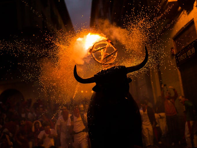"""A flaming fake bull """"Toro de fuego"""" runs after revelers during the 2014 San Fermin fiestas in Pamplona, Spain, Wednesday, July 9, 2014. Revelers from around the world arrive to Pamplona every year to take part in some of the eight days of the running of the bulls.  (AP Photo/Andres Kudacki)"""