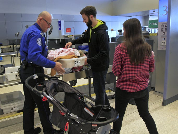 TSA supervisor Paul Costner, left, helps travelers with a baby through security at a security checkpoint in the Indianapolis International Airport, Wednesday, December 18, 2013.  Indianapolis International Airport is AmericaÕs best, or at least it has the best security checkpoints, says Travel + Leisure Magazine, which surveyed its readers as to where itÕs easiest to get through check-in and security.