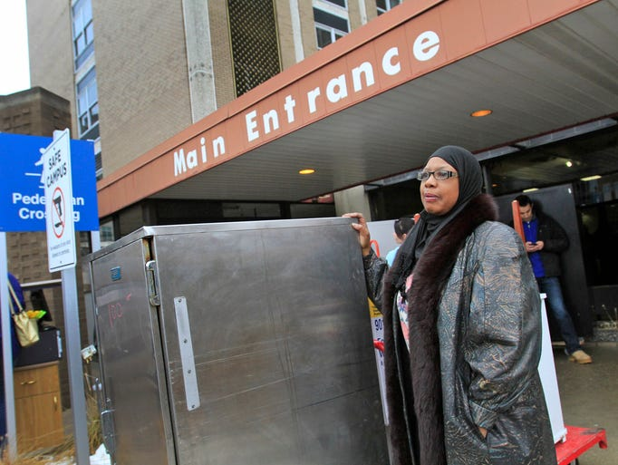Lana Lewis-Talib waits for her husband to haul off her new warmer or proofer she bought during the first day open to the public for the sale of non-medical items at Wishard Hospital, Saturday, January 11, 2014. She hopes to open a bakery using this oven for hot yeast rolls or for baking items that need to rise.  Rooms and hallways were lined with items for sale, open to the public Saturday and Sunday.  Anything left over will be given to not-for-profit organizations on Monday, January 13, 2014.