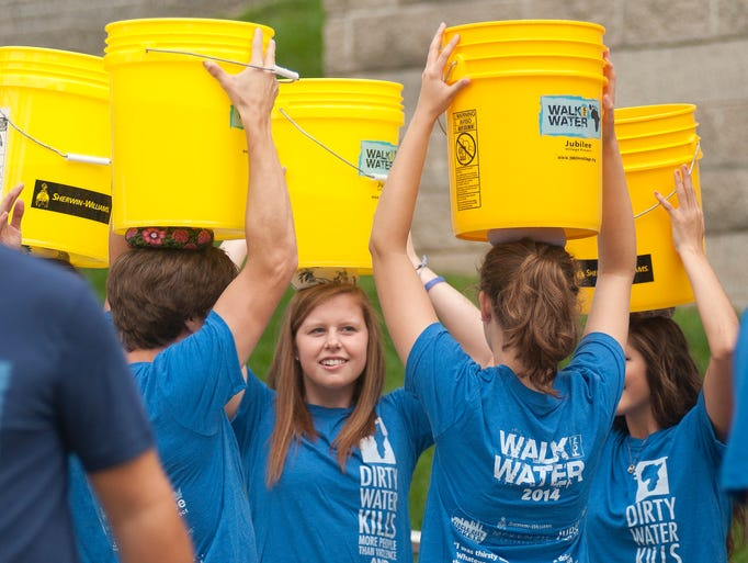 Ashley Cox and her friends carry canal water on their heads during the third annual Walk for Water event downtown, Saturday, Aug. 2, 2014. The event raised money for a community clean-water well in Kager, Kenya. Attendees walked from American Legion Mall to the canal, filled buckets with water and walked back to the mall, simulating the path villagers without clean water have to take every day.