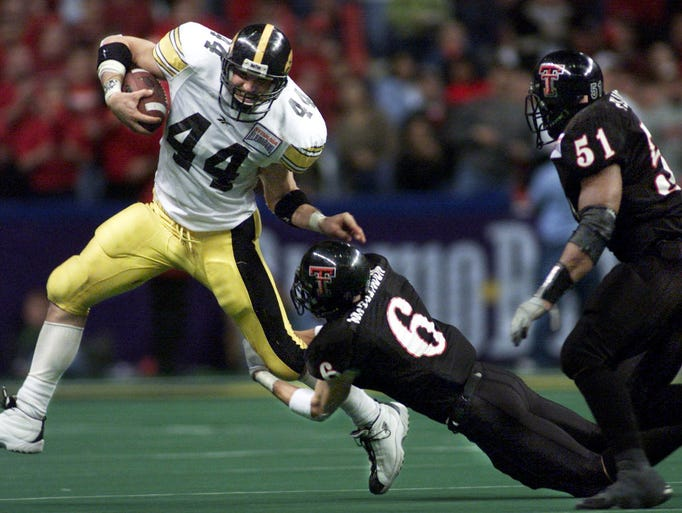 Iowa's Dallas Clark tries to break a tackle by Texas Tech's Paul McClendon as Tech's Lawrence Flugence chaces during Iowa's win over Tech in the Alamo Bowl in San Antonio, Texas in 2001.